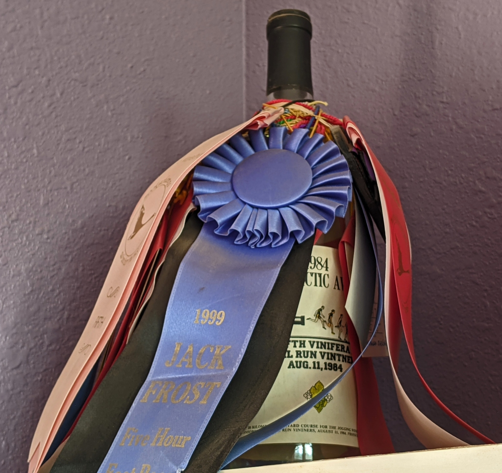 Wine bottle holding race ribbons and medals.