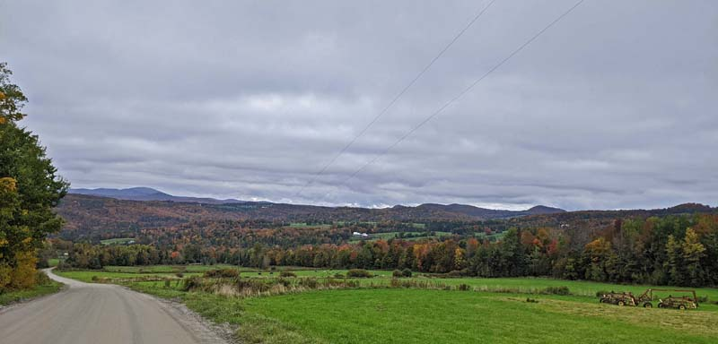 rural Vermont scenery of fields, trees, distant mountains and dirt road